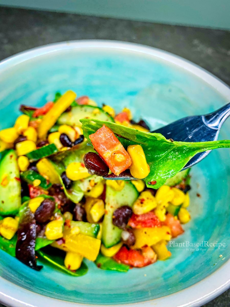 Recipe for a oil free vegan side salad that includes beans, corn, vegetables with a ginger orange dressing.